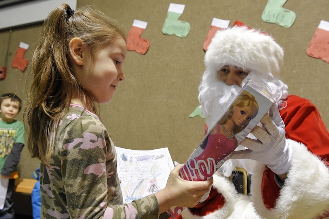 Santa Claus, played by Marine Corps Sgt. Mauricio Sandoval, gives a toy to a girl during a Toys for Tots event in Nikolai, Alaska, Dec. 11, 2015. Sandoval is assigned to Delta Company, 4th Law Enforcement Battalion. U.S. Air Force photo by Alejandro Pena