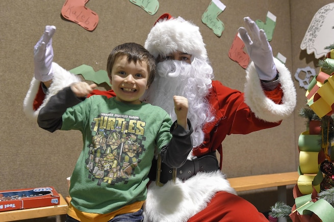 Xavier Hall, 4, takes a photo with Santa Claus, played by Marine Corps Sgt. Mauricio Sandoval, during a Toys for Tots event in Nikolai, Alaska, Dec. 11, 2015. Sandoval is assigned to Delta Company, 4th Law Enforcement Battalion. U.S. Air Force photo by Alejandro Pena