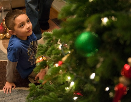 Timmy Payne admires his work on his family Christmas tree at his home in Mountain Home, Idaho, Dec. 5, 2015. At the young age of seven, Timmy has already experienced separation from both of his parents due to multiple deployments. (U.S. Air Force photo by Airman 1st Class Jessica H. Evans/RELEASED)