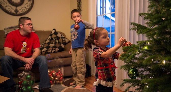 Tech. Sgt. Zachary Payne, 389th Aircraft Maintenance Unit weapons expeditor, watches his son and daughter decorate their family Christmas tree in Mountain Home, Idaho, Dec. 5, 2015. Payne's wife is currently deployed, so the family sent her a tree of her own to decorate while she's away. (U.S. Air Force photo by Airman 1st Class Jessica H. Evans/RELEASED)
