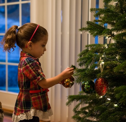 Yai Payne hangs an ornament on her family Christmas tree in Mountain Home, Idaho, Dec. 5, 2015. For Yai, this is the first time she has been separated from her mother due to a deployment. (U.S. Air Force photo by Airman 1st Class Jessica H. Evans/RELEASED)