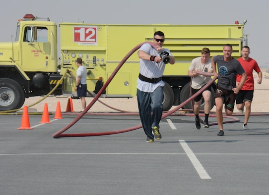 Deployed service members participate in the annual Battle of the Badges competition at Al Udeid Air Base, Qatar Dec. 21. The competition consisted of numerous events over four days including firefighter, medical and security forces career field challenges, as well as a fitness challenge. The 379th Expeditionary Civil Engineer Squadron fire team took first place in the competition. (U.S. Air Force photo by Tech. Sgt. James Hodgman/Released)