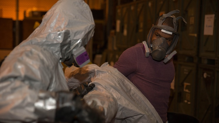 A Marine from Marine Wing Support Squadron 171 assists Sgt. Deedmund Nettles, left, food service specialist with MWSS-171, in removing his personal protective equipment during Hazardous Waste Operations and Emergency Response training at Marine Corps Air Station Iwakuni, Japan, Dec. 18, 2015. The course covered topics such as the hazards associated with working around chemicals, how to locate information on different chemicals, and the four aspects of planning and organizing a hazardous waste site, which are organizational structure, work plan, safety meetings and inspections. This training provided Marines with the proper knowledge to identify contain and clean up hazardous materials.