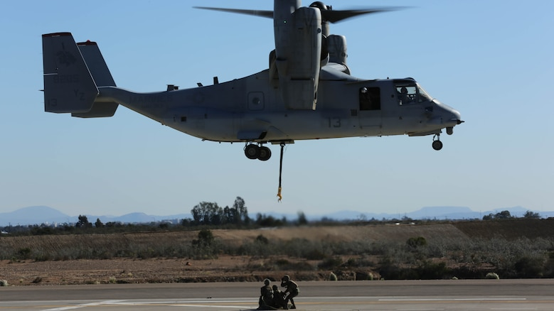 Marines with Combat Logistics Battalion 5 prepare to attach a simulated cargo of 1,400 pounds to an MV-22B Osprey with Marine Medium Tiltrotor Squadron 363 aboard Marine Corps Air Station Miramar, Calif., Dec. 16, 2015. Daytime external lift training prepares the Marines with VMM-363 to attach cargo to the aircraft which helps qualify more air crew in the mission-essential task of rapid insertion and extraction for the squadron.