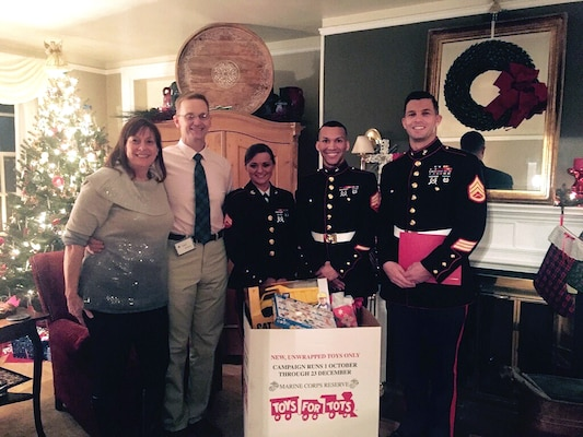Toys for Tots donations are collected by, from left to right, Laura McLeod, Air Force Brig. Gen. Mark McLeod, Marine Cpl. Chelsea Propes, Marine Sgt. Robert Bradley and Marine Staff Sgt. Andrew Eichelberger. Defense Logistics Agency Energy employees contributed more than 150 toys during the DLA Energy commander's holiday reception at Fort Belvoir, Virginia, Dec. 19.