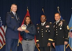 DLA director Air Force Lt. Gen. Andy Busch, left, presents Kareneshia Stubblefield, distribution process worker at Distribution Norfolk, Va., with the Top 10 Employee award at the 48th annual employee recognition ceremony Dec. 10. Distribution's commander Army Brig. Gen. Richard Dix, second from right, and DLA's Senior Enlisted Leader Army Command Sgt. Maj. Charles Tobin, right, were also on-hand to present the award.