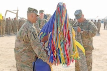 "Lt. Col. Andy Sanchez, left, and Command Sgt. Maj. Pablo Coronado, right, uncase the colors of the 1st Battalion, 18th Infantry Regiment, 2nd Armored Brigade Combat Team, 1st Infantry Division, during their transfer of authority ceremony Nov. 4 at Camp Buehring, Kuwait.  The ceremony officially signified that the ""Vanguard"" battalion assumes responsibilities for theater-specific missions in Southwest Asia.  The battalion departed Fort Riley in October."