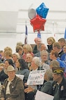 Crowd members hold signs in support of Vietnam veterans Nov. 6 during the Vietnam Veterans Welcome Home Ceremony at Fort Riley's Marshall Army Airfield. Soldiers, veterans' family members and members of the Flint Hills community filled a hangar as the Vietnam veterans were welcomed home in a long overdue celebration.