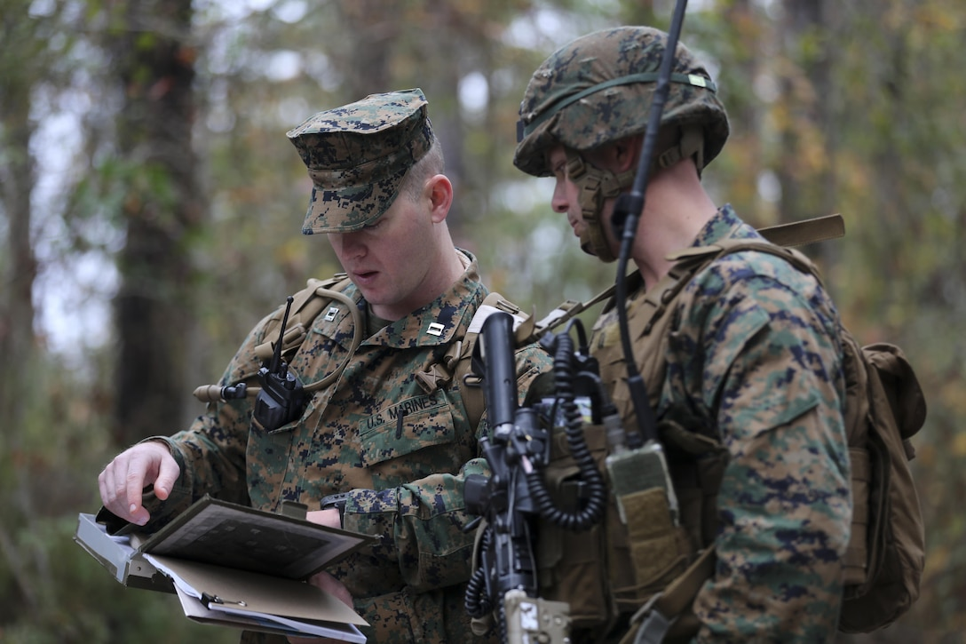 (Left) Captain Jerald Feehery, a project officer for Marine Corps Warfighting Laboratory, discusses tactics with Capt. Patrick Parks, the Lima Company commander with 3rd Battalion, 6th Marine Regiment, prior to entering the Military Operation in Urban Terrain during a limited objective experiment at Camp Lejeune, N.C., Dec. 8, 2015. The Marine Corps Warfighting Laboratory worked with 3rd Bn., 6th Marines, and 1st Battalion, 10th Marine Regiment, to test artillery and infantry integration tactics. During the experiment, the company landing team attacked from near the Onslow Beach landing site towards the objective of the Military Operation in Urban Terrain training center. (U.S. Marine Corps photo by Cpl. Michael Dye/Released)