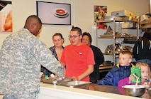 Pfc. Keith Wrenn, 1st Combined Arms Battalion, 18th Infantry Regiment, 2nd Armored Brigade Combat Team, 1st Infantry Division goes through the line taking some of the mixed vegetables which are always in supply at the No Dough Din¬ners. The dinner was hosted by volunteers of the USO Fort Riley and sponsored by Army Community Service and the Association of the United States Army. It took place in the Culinary Arts building Nov. 16.