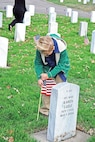 Jett Feider, 8, son of Kate and 1st Sgt. Pete Feider, Warrior Transition Battalion, places a flag at a grave in honor of Vet¬erans Day Nov. 10 at the Post Cemetery.