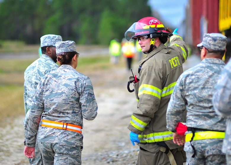 A Panama City Fire Department firefighter talks to Tyndall Airmen during a training exercise Dec. 17 at the Panama City Bay Line Railroad. More than 40 members of Tyndall joined over 150 people from local agencies to participate in an extensive train environment exercise. (U.S. Air Force photo by Senior Airman Dustin Mullen/Released)