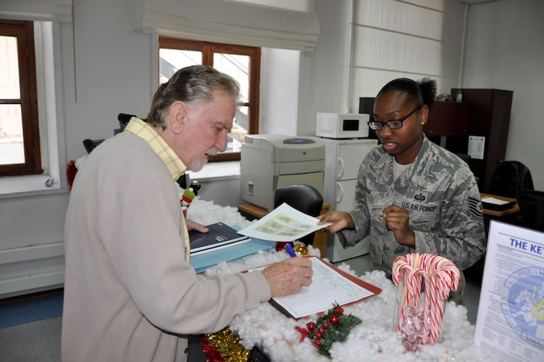 Tech. Sgt. Nancy Rouse, 425th Air Base Squadron commander's support staff, issues a ration card to Jim Kutrubis, 425th Air Base Squadron services director, Dec. 14, 2015, at Izmir Air Station, Turkey.  Ration cards are required to purchase liquor and tobacco at military exchanges, commissaries and shoppettes at overseas bases. (U.S. Air Force photo by Tanju Varlıklı)