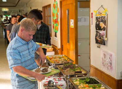 Lance Cpl. David Ryan from Tallahassee, Florida, fills his plate during a Christmas party thrown by the Hikariga Oka Nursing Home in Kin Town, Okinawa, Japan, Dec. 18, 2015. The nursing home hosts the party annually as thanks for 7th Communication Battalion's continuous community outreach projects. Since 1994, Marines with the battalion have regularly volunteered to help maintain the home's grounds and organized routine cleanups and maintenance. Ryan is a field radio operator with 7th Comm. Bn., III Marine Expeditionary Force Headquarters Group, III MEF.(U.S. Marine Corps Photo by Cpl. Devon Tindle/Released)