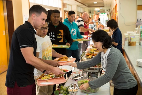Junko Kurata, right, serves salad to Cpl. Jonathan Koren during a Christmas Party thrown by the Hikariga Oka Nursing Home in Kin Town, Okinawa, Japan, Dec. 18, 2015. The nursing home hosts the Christmas party annually to pay thanks for 7th Communication Battalion continuous contributions and community outreach projects. Since 1994, Marines with the battalion have regularly volunteered regularly by organizing routine cleanups and maintenance for the home and its surrounding area. Kurata is from Kin town and is a nurse at the nursing home. Koren is from Allentown, Pennsylvania and is a digital wideband repairer with 7th Comm. Bn., III Marine Expeditionary Force Headquarters Group, III MEF. (U.S. Marine Corps Photo by Cpl. Devon Tindle/Released)