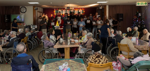 Marines with 7th Communication Battalion sing Christmas carols to the residents at Hikariga Oka Nursing Home during a Christmas Party thrown by the nursing home for the Marines at Hikariga Oka Nursing Home in Kin Town, Okinawa, Japan, Dec. 18, 2015.The nursing home hosts the Christmas party annually to pay thanks for the battalion's continual community relations projects. Since 1994 Marines with the battalion regularly volunteers regularly to help maintain the home's grounds of the home and conduct organize routine cleanups and maintenance. The Marines are with 7th Comm. Bn., III Marine Expeditionary Force Headquarters Group, III MEF. (U.S. Marine Corps Photo by Cpl. Devon Tindle/Released)