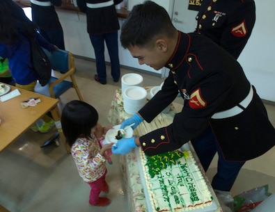 Lance Cpl. Tony McCandless, right, hands out cake to kids Dec. 19 at the Kin Town Social Welfare Center, Okinawa, Japan. Marines organized a toy drive through the Kin Town Single Parent Association to give back to their community by handing out gifts and cake to the children. McCandless is a radio maintainer with 3rd Intelligence Battalion, III Marine Headquarters Group, III Marine Expeditionary Force. (U.S. Marine Corps photo by Cpl. Isaac Ibarra/Released)