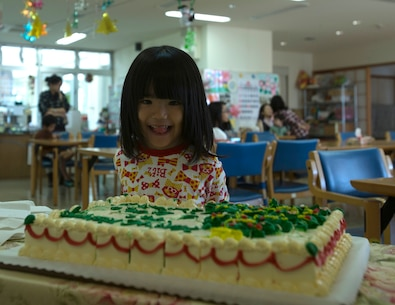 Satsuki Ashitomi eagerly waits for a piece of cake Dec. 19 at the Kin Town Social Welfare Center, Okinawa, Japan. Marines organized a toy drive through the Kin Town Single Parent Association to give back to their community by handing out gifts and cake to the children. The Marines are with 3rd Intelligence Battalion, III Marine Headquarters Group, III Marine Expeditionary Force. (U.S. Marine Corps photo by Cpl. Isaac Ibarra/Released)
