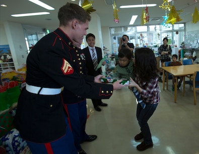 Cpl. Zachariah Mercer hands a present to a child Dec. 19 at the Kin Town Social Welfare Center, Okinawa, Japan. Marines organized a toy drive through the Kin Town Single Parent Association to give back to their community by handing out gifts and cake to the children. Mercer is a surveillance sensor operator with 3rd Intelligence Battalion, III Marine Headquarters Group, III Marine Expeditionary Force. (U.S. Marine Corps photo by Cpl. Isaac Ibarra/Released)