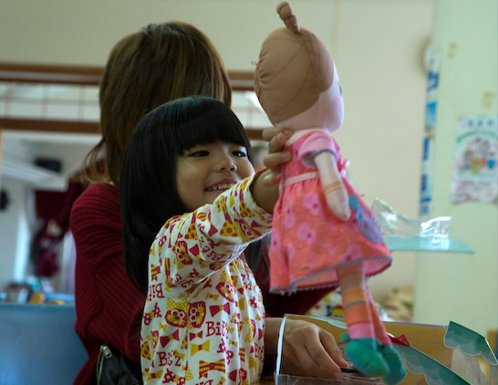 Satsuki Ashitomi plays with her new doll Dec. 19 at the Kin Town Social Welfare Center, Okinawa, Japan. Marines organized a toy drive through the Kin Town Single Parent Association to give back to their community by handing out gifts and cake to the children. The Marines are with 3rd Intelligence Battalion, III Marine Headquarters Group, III Marine Expeditionary Force. (U.S. Marine Corps photo by Cpl. Isaac Ibarra/Released)