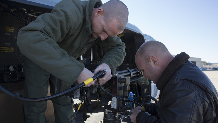 Two combat marksmanship trainer instructors with Marine Light Attack Helicopter Squadron 303, prepare an M134 GAU-17 Minigun prior to a formation flight and aerial gunnery shoot at Marine Corps Air Station Camp Pendleton, California, Dec. 17. Marines with HMLAT-303 flew a formation flight and conducted an aerial gunnery to shoot to give students the opportunity to refine basic skills needed to operate in the Fleet Marine Force.
