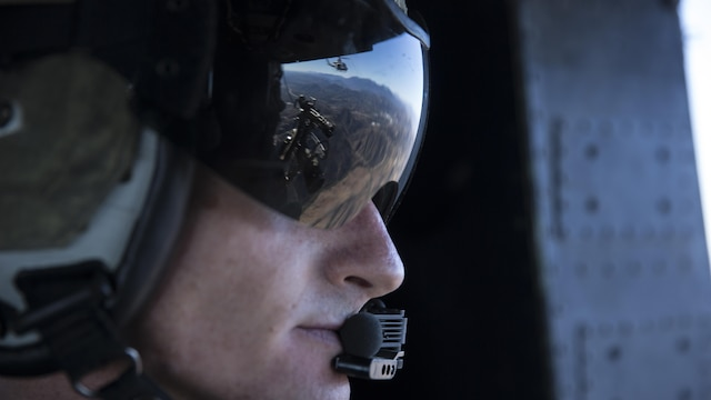Gunnery Sgt. Christopher Mulcahy, a combat marksmanship trainer instructor with Marine Light Attack Helicopter Training Squadron 303, looks out of a UH-1Y Huey during a formation flight above Marine Corps Base Camp Pendleton, California, Dec. 17. Mulcahy communicated the position of another Huey and other aircraft during the formation flight.