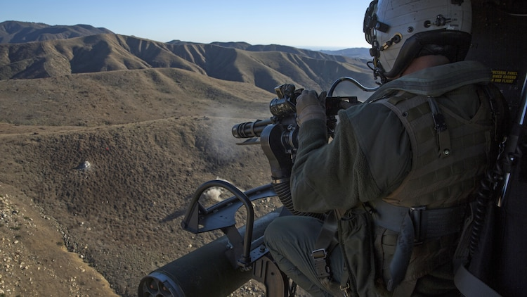 Gunnery Sgt. Christopher Mulcahy, a combat marksmanship trainer instructor with Marine Light Attack Helicopter Training Squadron 303, fires an M134 GAU-17 Minigun during an aerial gunnery shoot at Marine Corps Base Camp Pendleton, California, Dec. 17. Marines with HMLAT-303 flew a formation flight and conducted an aerial gunnery to shoot give students the opportunity to refine basic skills needed to operate in the Fleet Marine Force.