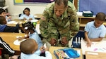 DLA Troop Support Commander Army Brig. Gen. Charles Hamilton greets students at Benjamin Franklin Elementary School during the organization's annual children's holiday party Dec. 10, 2015. More than 200 kindergarteners and first-graders participated in arts and crafts, games and received gifts donated by DLA Troop Support employees.