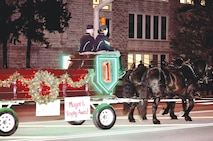 Spc. Nicole Fox and Sgt. Nathaniel Boyd, Commanding General's Mounted Color Guard, guide the unit's Percheron draft horse team, Jenny and Joy, on Dec. 4 down Poyntz Avenue in Manhattan, Kansas, during the Mayor's Spirit of the Holidays Lighted Parade.  The CGMCG won the Mayor's Trophy Award for the wagon's light and decoration display.