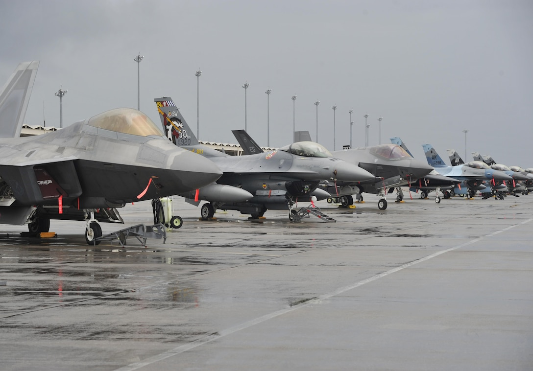 An F-22 Raptor and a T-38 Talon from Tyndall Air Force Base, Fla., F-16 Fighting Falcons from Shaw AFB, S.C. and Eielson AFB, Alaska, and an F-35 Lightning II from Eglin AFB, Fla., sit on the flightline at Tyndall AFB Dec. 17, 2015, during exercise Checkered Flag 16-1. Checkered Flag 16-1 is a large force exercise that simulates employment of a large number of aircraft from a simulated deployed environment. (U.S. Air Force photo/Senior Airman Sergio A. Gamboa)