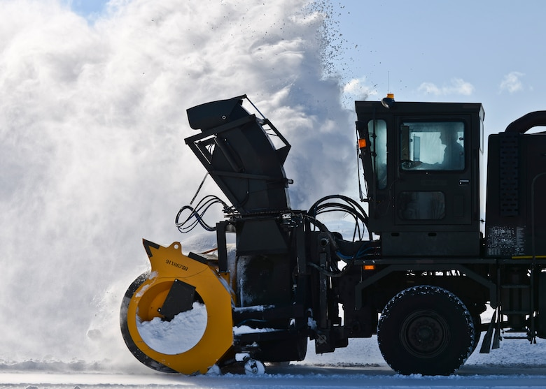 A member of the 28th Civil Engineer Squadron operates a snow blower to clear the flightline at Ellsworth Air Force Base, S.D., Dec. 16, 2015. The airfield is the 28th CES's biggest mission and number one priority during winter months. (U.S. Air Force photo/Airman Sadie Colbert)