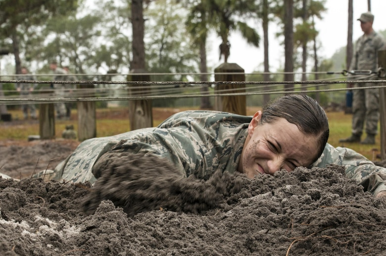 Second Lt. Lizette Wu, assigned to the 820th Base Defense Group, low crawls through mud as part of an obstacle course during an air assault assessment Dec. 15, 2015, at Camp Blanding, Fla. Airmen had to crawl without letting any part of their body touch the metal wires hung above. (U.S. Air Force photo/Airman 1st Class Lauren M. Johnson)