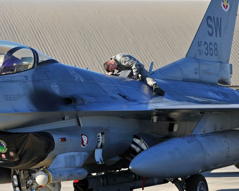 A 77th Aircraft Maintenance Unit dedicated crew chief from Shaw Air Force Base, S.C. performs maintenance on an F-16 Fighting Falcon Dec. 15, 2015, on the flightline at Tyndall AFB, Fla. The F-16 is a compact, multi-role fighter aircraft. It is highly maneuverable and has proven itself in air-to-air combat and air-to- surface attack. (U.S. Air Force photo/Senior Airman Sergio A. Gamboa)