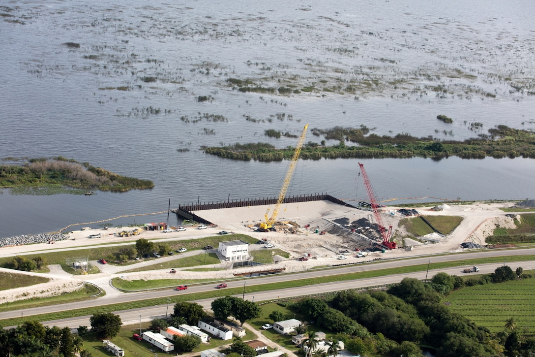 "With Lake Okeechobee in the background, crews work to replace a water control structure, or ""culvert"" in Herbert Hoover Dike along Highway 27 near Clewiston.  The culvert replacements ongoing require significant preparation of the site, to include installation of a temporary cofferdam to hold back water while crews work on the earthen structure."