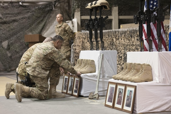 U.S. service members pay their respects during a ceremony on Bagram Airfield, Afghanistan, Dec. 23, 2015, to honor six airmen killed in a vehicle bomb attack on their patrol outside Bagram. U.S. Air Force photo by Tech. Sgt. Robert Cloys