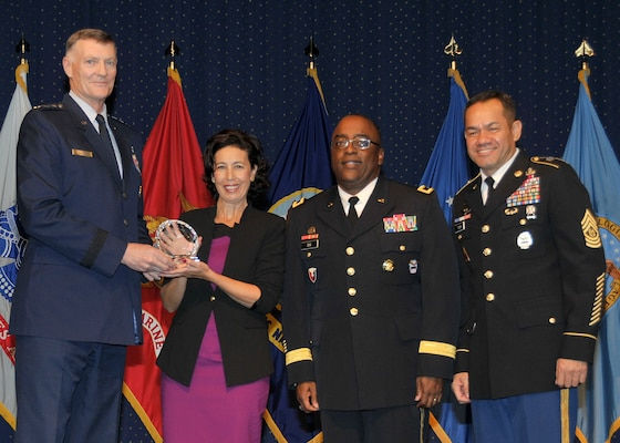 DLA director Air Force Lt. Gen. Andy Busch, left, presents Eva Maria Perez Sanchez, administrative support assistant at Distribution Sigonella, Italy, with the Top 10 Employee award at the 48th annual employee recognition ceremony Dec. 10. Distribution's commander Army Brig. Gen. Richard Dix, second from right, and DLA's Senior Enlisted Leader Army Command Sgt. Maj. Charles Tobin, right, were also on-hand to present the award.