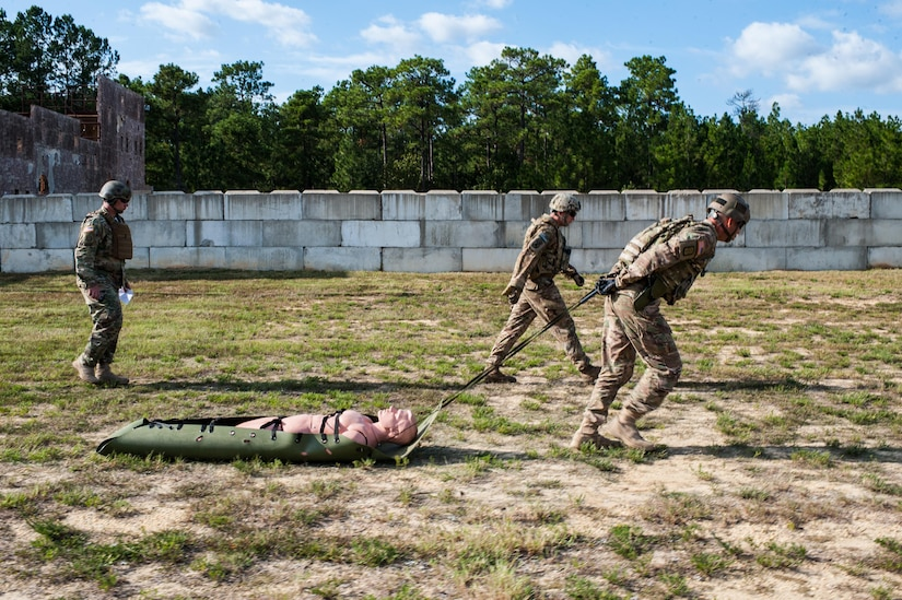 Master Sgt. Russell Moore, with the 416th Theater Engineer Command and a member of the U.S. Army Reserve Marksmanship Team, begins the Stress Fire event by pulling a 175-pound mannequin on the second day of the U.S. Army Forces Command Weapons Marksmanship Competition Sept. 22, 2015, at Fort Bragg, N.C. The three-day FORSCOM competition features 27 marksmen from the U.S. Army, U.S. Army Reserve, and the National Guard in events for the M9 pistol, the M4A1 rifle, and the M249 SAW, or Squad Automatic Weapon, to recognize Soldiers who are beyond expert marksmen. The multi-tiered events challenge the competitors' ability to accurately and quickly engage targets in a variety of conditions and environments. (U.S. Army photo by Timothy L. Hale/Released)