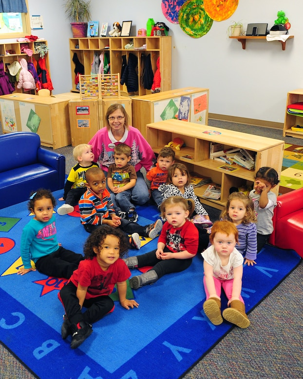 "Catherine Miller, a child and youth program assistant with the 509th Force Support Squadron Susie Skelton Child Development Center (CDC), sit with her students prior to story time at Whiteman Air Force Base, Mo., Dec. 22, 2015. In 2010, Miller began a drive to help veterans spending the holiday season alone. This year, 13 different classrooms at the CDC ""adopted"" a veteran by collecting items and making them cards. (U.S. Air Force photo by Airman 1st Class Jazmin Smith)"