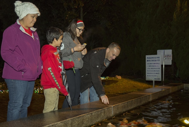 From left to right, Rhonda Kirk, program assistant with the Youth and Teen Center, Anna Kirk, and Kris Kirk, Mathew C. Perry Elementary School students, and Gunnery Sgt. Isaiah Kirk, cyber network chief with Headquarters and Headquarters Squadron at Marine Corps Air Station Iwakuni observe a Koi pond at the Hiroshima Botanical Garden in Hiroshima City, Japan, Dec. 23, 2015. The visit afforded residents the opportunity to explore various exhibits and view the festive displays at the garden.