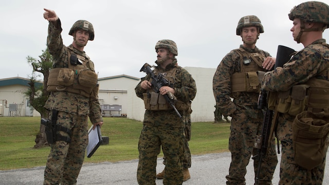 Capt. Albert Bellamy, far left, the commanding officer of Golf Battery, Battalion Landing Team 1st Battalion, 5th Marines, 31st Marine Expeditionary Unit, points to where he wants a security checkpoint setup at Camp Courtney in Okinawa, Japan, Dec. 15, 2015. The battery was training to distribute food and water as part of a humanitarian assistance and disaster relief operation when the crowd, played by other Marines, became unruly. A quick reaction force was called to help restore order and continue to distribute supplies. The HADR training was conducted as part of the 31st MEU's Marine Expeditionary Unit Exercise. Capt. Bellamy is from Wadsworth, Ohio.