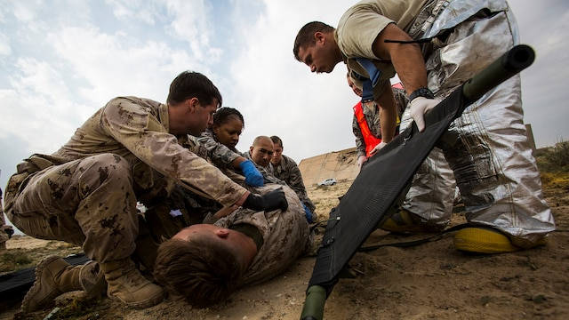 U.S. Navy and Air Force medical personnel load a simulated casualty onto a stretcher during a mass casualty exercise at an undisclosed location in Southwest Asia, Dec. 23, 2015. Canadian forces, U.S. Air Force and Army medical personnel, along with U.S. Marines and Navy corpsmen with Special Purpose Marine Air Ground Task Force – Crisis Response – Central Command, participated in the joint exercise to hone the coalition's medical response capabilities.  SPMAGTF-CR-CC is currently deployed to the U.S. Central Command area of responsibility with a mission spanning 20 nations.