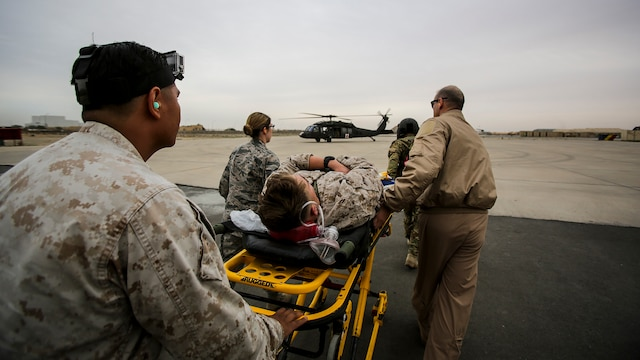 "U.S. Air Force and Navy medical personnel prepare to load a simulated casualty onto a UH-60 ""Black Hawk"" helicopter during a mass casualty exercise at an undisclosed location in Southwest Asia, Dec. 23, 2015. Canadian forces, U.S. Air Force and Army medical personnel, along with U.S. Marines and Navy corpsmen with Special Purpose Marine Air Ground Task Force – Crisis Response – Central Command, participated in the joint exercise to hone the coalition's medical response capabilities.  SPMAGTF-CR-CC is currently deployed to the U.S. Central Command area of responsibility with a mission spanning 20 nations."