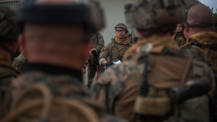 Cpl. Bryan Loos, a Maritime Raid Force intelligence analyst, briefs MRF Marines before conducting a raid Dec. 10, 2015, on Camp Hansen, Okinawa, Japan. The raid was part of the MRF's Interoperability Exercise 16-1. INTEROP brings together all of the elements of the MRF and the 31st Marine Expeditionary Unit so they can identify any deficiencies, work through them, and build standard operating procedures. Loos, from Stafford, Virginia, is with the MRF, 31st MEU.