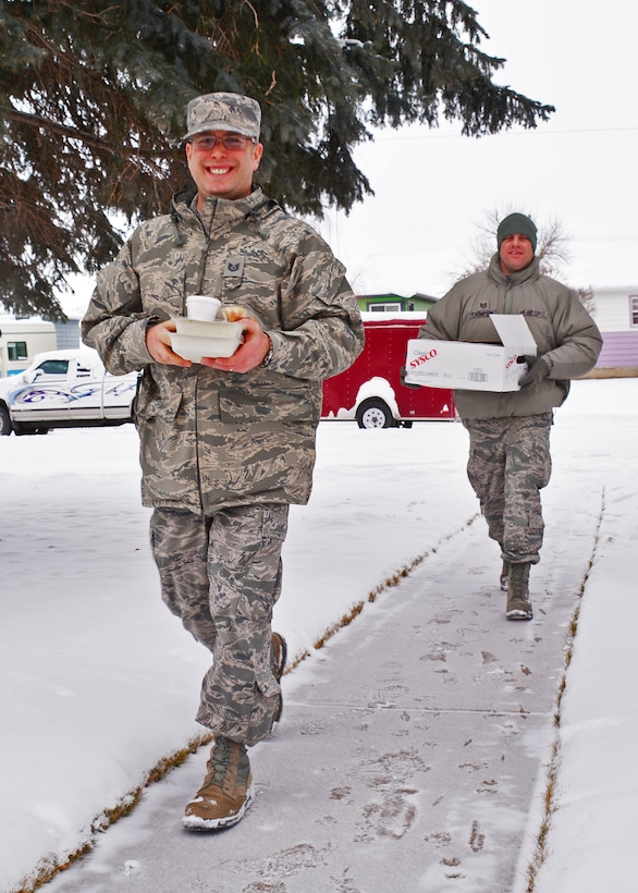 120th Communications Flight members Tech. Sgt. Brandon Musgrove and Tech. Sgt. Justin Thompson volunteer to deliver food for the Meals on Wheels program as a community service project during the holiday season in Great Falls, Mont. Dec. 18, 2015. (U.S. Air National Guard photo by Senior Master Sgt. Eric Peterson/Released)