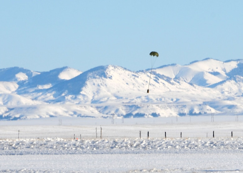 A parachuted training bundle dropped by a C-130 Hercules transport aircraft assigned to the 120th Airlift Wing of the Montana Air National Guard drifts to the ground near the target at the Charging Charlie Drop Zone located at Malmstrom Air Force Base, Mont. Dec. 17, 2015. (U.S. Air National Guard photo by Senior Master Sgt. Eric Peterson/Released)