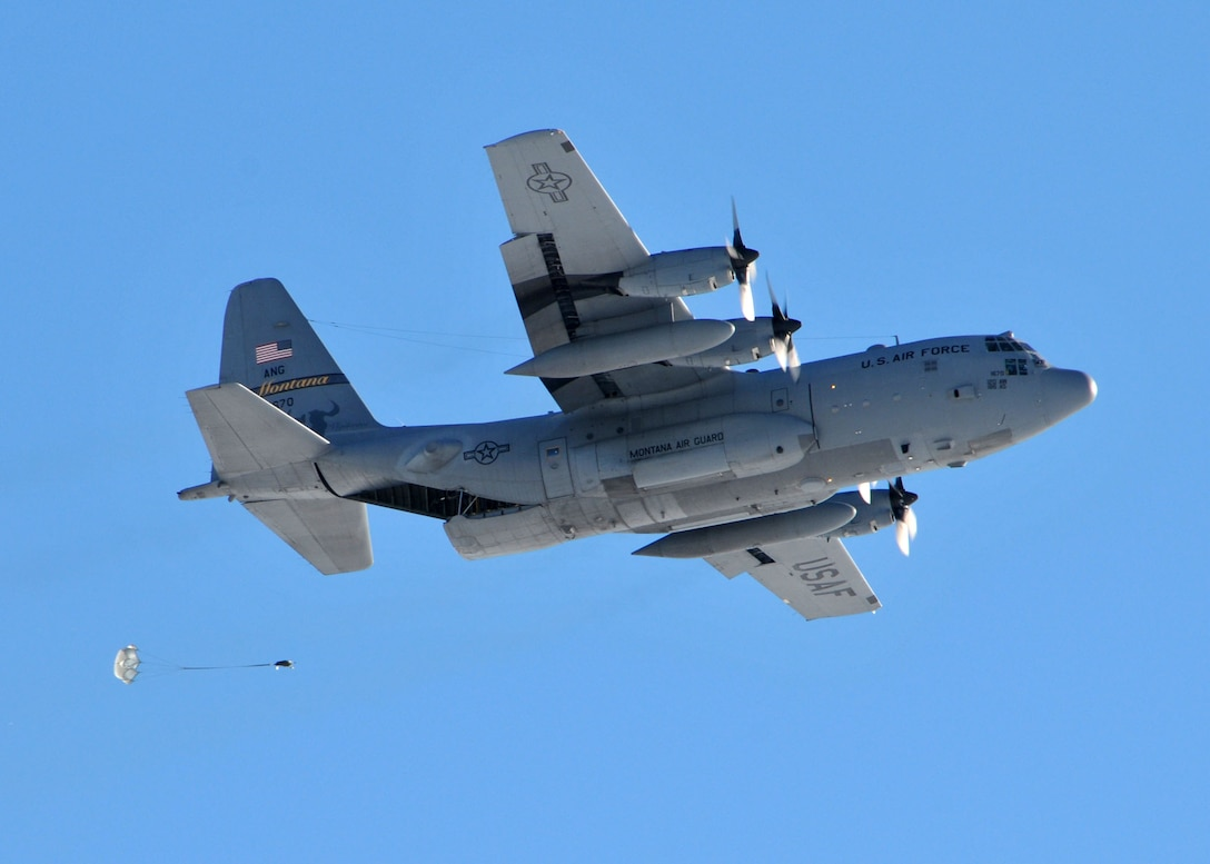A C-130 Hercules transport aircraft assigned to the 120th Airlift Wing of the Montana Air National Guard drops a parachuted training cargo bundle at the Charging Charlie Drop Zone located at Malmstrom Air Force Base, Mont. Dec. 17, 2015. (U.S. Air National Guard photo by Senior Master Sgt. Eric Peterson/Released)