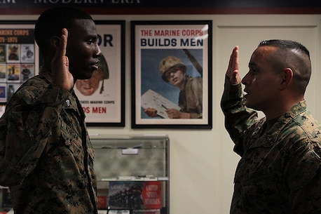 Cpl. Charles Morgan, personnel clerk at the district headquarters, repeats after CWO4 Felipe Aguilar, personnel officer at the district headquarters, during his reenlistment December 22, 2015, in the 6th Marine Corps District Museum aboard Parris Island, S.C. (Official Marine Corps photo by Cpl. John-Paul Imbody)