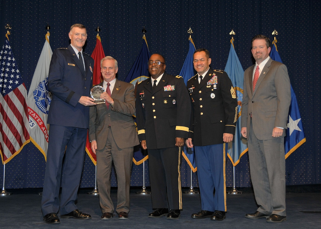 DLA director Air Force Lt. Gen. Andy Busch, left, presents Perry Knight, chief integration officer at Defense Logistics Agency Distribution, with the Leader of the Year award at the 48th annual employee recognition ceremony Dec. 10. Distribution's commander Army Brig. Gen. Richard Dix, third from right, DLA's Senior Enlisted Leader Army Command Sgt. Maj. Charles Tobin, second from right, and Brad Bunn, right, Director of Human Resources, were also on-hand to present the award.