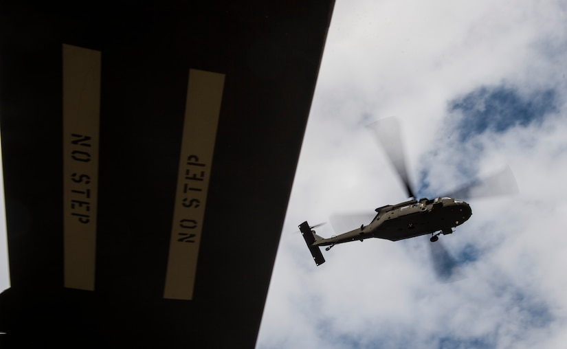 A UH-60 Black Hawk from the 3rd Combat Aviation Brigade flies over a dock Dec. 28, 2015 at Joint Base Charleston, S.C. Weapons Station. More than 20 helicopters returned to the U.S. from various United States European Command bases via cargo ship. The 841st Transportation Battalion from Joint Base Charleston unloaded the helicopters and the 3rd CAB flew the aircraft back to their home  station, Hunter Army Airfield, Ga. (U.S. Air Force photo/Senior Airman Jared Trimarchi)