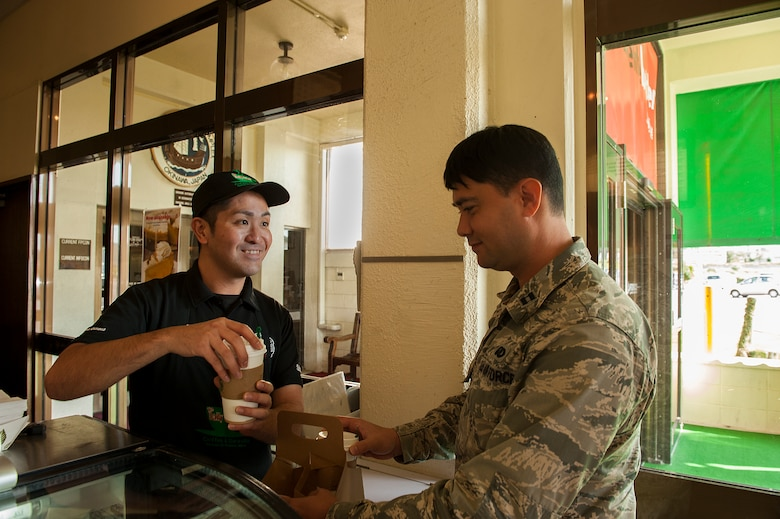 U.S. Air Force Capt. Joshua Caragan, 18th Wing equal opportunity officer, gets coffee from Koji Kamekawa, Daily Grind Coffee Shop cashier, in the Rocker NCO Club, Dec. 30, 2015, at Kadena Air Base, Japan. The Rocker NCO Club is closing its doors to make way for a brand new facility coming in 2017. (U.S. Air Force photo by Airman 1st Class Corey M. Pettis)